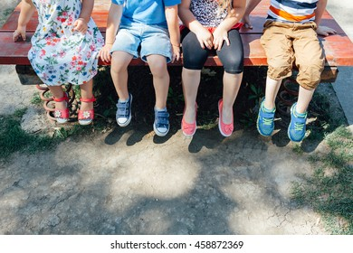 Kids sitting at the playground. Legs in close up with copy space.
