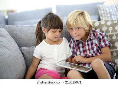 Kids sitting in sofa and playing with tablet