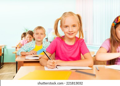 Kids sitting at table in classroom and writing