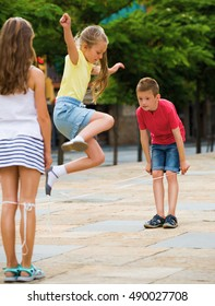Kids skipping on chinese jumping elastic rope in yard