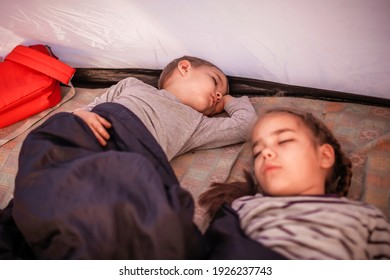 Kids sleeping in the camping tent during family local getaway. Children in the sunrise light, overnight in the wild nature. Healthy lifestyle, green local tourism and vacations, campsite. Soft focus