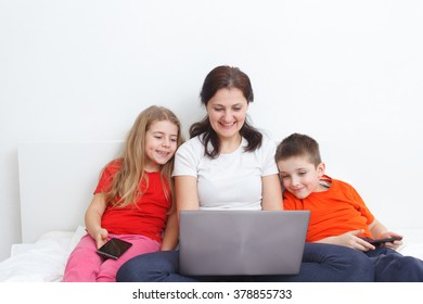 kids with smartphones watching at mom's laptop