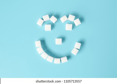 Kids smiling face with tooth decay made of sugar cubes on blue background. Sugar is the cause of tooth decay. concept.