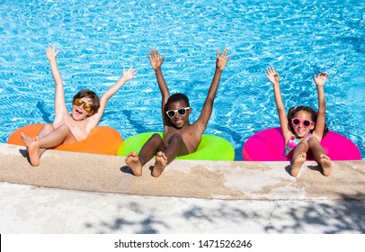 kids smiling and happy in the pool on a sunny summer day