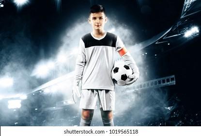 Kids - soccer champion. Boy goalkeeper in football sportswear on stadium with ball. Sport concept.