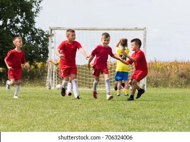 Kids soccer football - little children players celebrating after goal at  soccer field