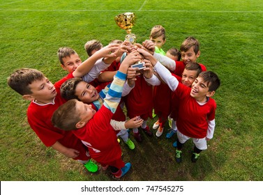 Kids soccer football - young children players celebrating with a trophy after match on soccer field