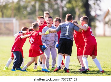 Kids soccer football - young children players celebrating in hug after victory