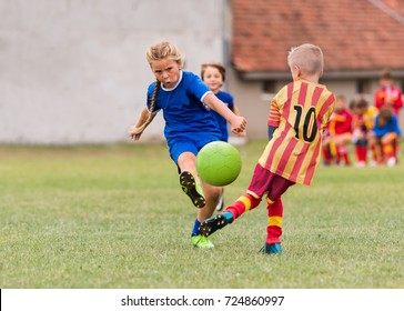 Kids soccer football - young little girl is shooting ball at soccer field