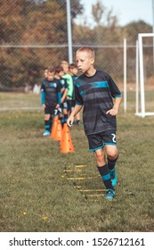 Kids soccer players Jogging and jump between marker for football training. Ladder Drills Exercises for Football Soccer team. Young player exercises on ladder drills.