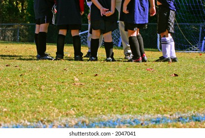 Kids' soccer team in coach's huddle