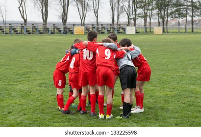 kids soccer team in huddle
