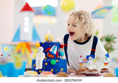 Kids space theme birthday party with cake and cupcakes. Rocket, solar system planet and spaceship decoration for child event. Little boy in astronaut costume blowing candles and opening presents.