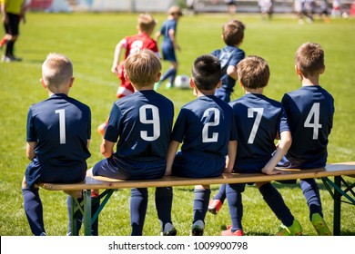 Kids sport team sitting on a bench. Group of kids soccer players. Children football club. Football soccer tournament game for children. Boys kicking soccer ball on grassy pitch. Children play sports o