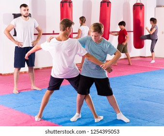 Kids in sportswear exercising self-protection techniques in pair during class at gym