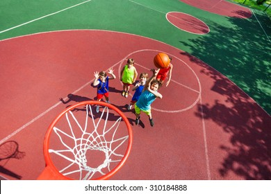 Kids stand on ground and ball flying to the basket