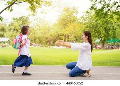 Estudiante de niños corriendo a las manos de su madre para abrazarla después de volver a la escuela.