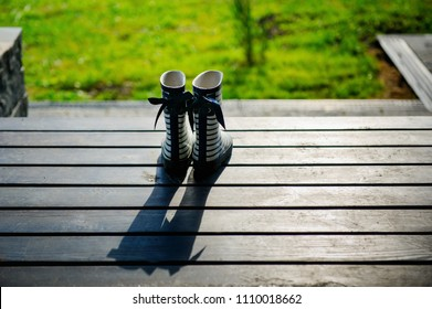 Kids style rain boots on a wooden sunlit terrace with long shade