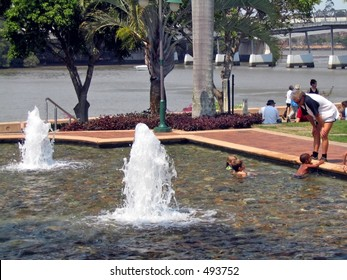 Kids swimming in a fountain, across the river from Brisbane