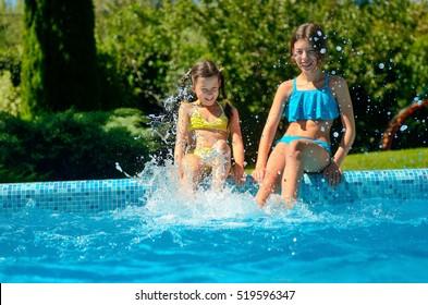 Los niños en la piscina se divierten, las niñas chapotean en el agua, los niños activos felices en vacaciones familiares
