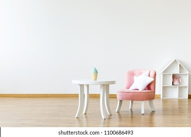 Kid's table and chair with a star pillow in a white, empty room interior with a dollhouse in the background. Place for your product
