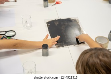 Kids take their fingerprints with black paint.
