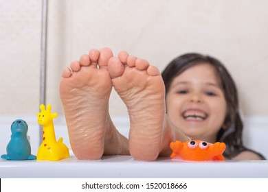 Kids taking bubble bath. Child bathing in bathtub. Little girl playing with water. Rubber duck in foam bath