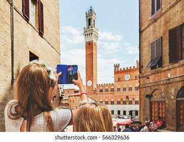 Kids taking picture with the smartphone of Piazza del Campo, Siena, Italy