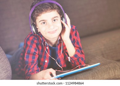 Kids and technology concept with young boy listening to his favorite music using his tablet