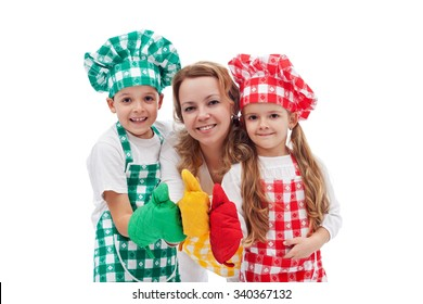Kids and their mother preparing food together - dressed as chefs, isolated