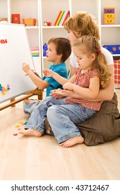 Kids with their mother sitting on the floor learning numbers and playing