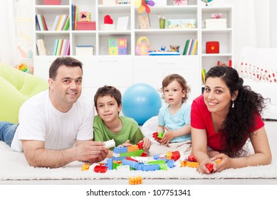 Kids with their parents playing at home - family portrait, focus on the children