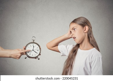 Kids time to go to bed. Portrait mom showing daughter clock that it is late. She does not like isolated grey wall background. Face expression emotions. Difficult parenting concept. Children's schedule