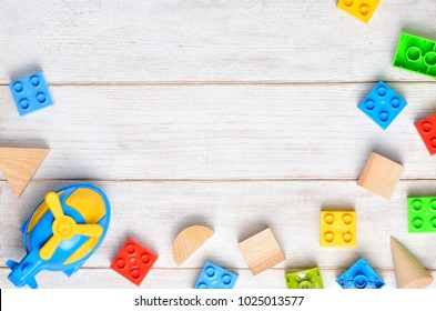 Kids toys background. Colorful blocks and plane on white wooden background. Space for text.