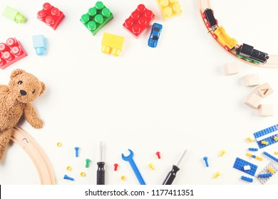 Kids toys background with construction blocks and cubes, toys tools, wooden train and teddy bear