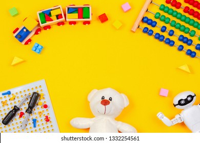 Kids toys background. Teddy bear, wooden train, robot, colorful blocks, toy tools kit, abacus on yellow background