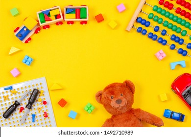 Kids toys background. Teddy bear, wooden train, colorful blocks, toy tools kit, cars, abacus on yellow background