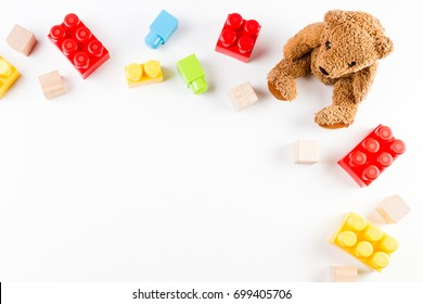 Kids toys background with teddy bear and colorful bricks. Top view