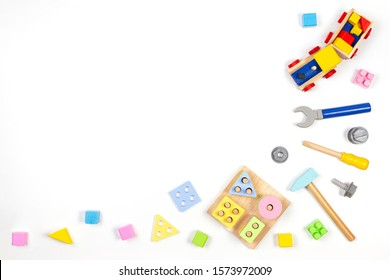 Kids toys background. Wooden train, educational geometric stacking blocks toy and wood tools kit on white background. Top view, flat lay