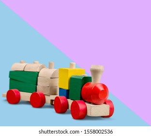 Kids toys: pyramid, wooden blocks, bear, train frame on colored background. Top view. Flat lay. Copy space for text