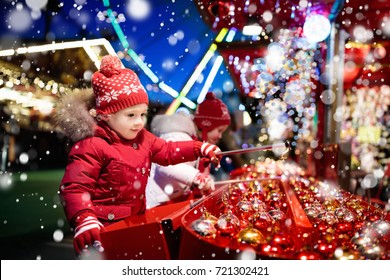 Kids at traditional Christmas fair. Children and Xmas market on snowy evening. Family shopping Christmas gifts and presents. Boy and girl play hook a bauble game. Winter fun. Advent time in Europe.