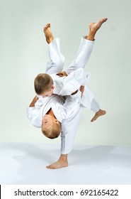 Kids are training throws of judo in judogi