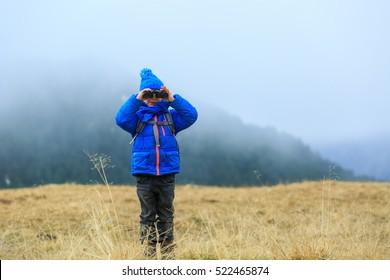 kids travel - little boy with binoculars hiking in mountains