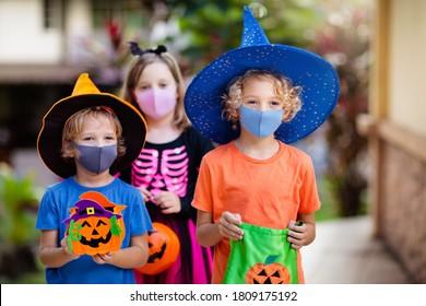 Kinder tricken oder behandeln zu Halloween Kostüme und Gesichtsmaske. Kinder in Kleidung mit Süßigkeiten Eimer in der Koronavirus-Pandemie. Kleiner Junge und Mädchen Trick oder Behandlung mit Kürbislattern. Herbsturlaub Spaß.