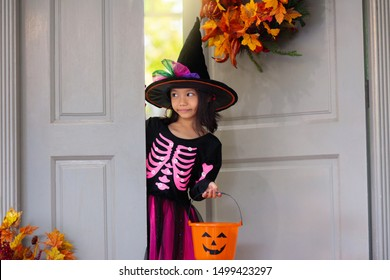 Kids trick or treat on Halloween. Little Asian girl at decorated house door with autumn leaf wreath and pumpkin lantern. Child in witch and skeleton costume and hat with candy bucket. Fall decoration.