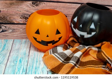 Kids trick or treat pumpkin candy pails placed on a cozy plaid scarf
