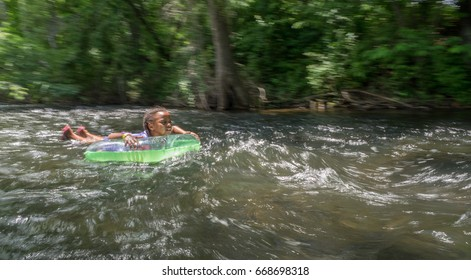 Kids tubing down river on hot summer day