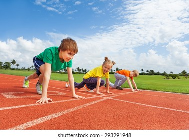 Kids in uniforms on bended knee ready to run
