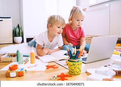 Kids using computer online technology to art creative, drawing or making crafts. Preschool children distance online education. Family leisure with little children at home or daycare.