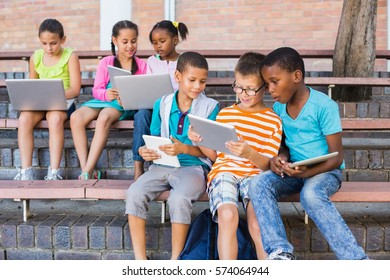 Kids using digital tablet and laptop on bench at school